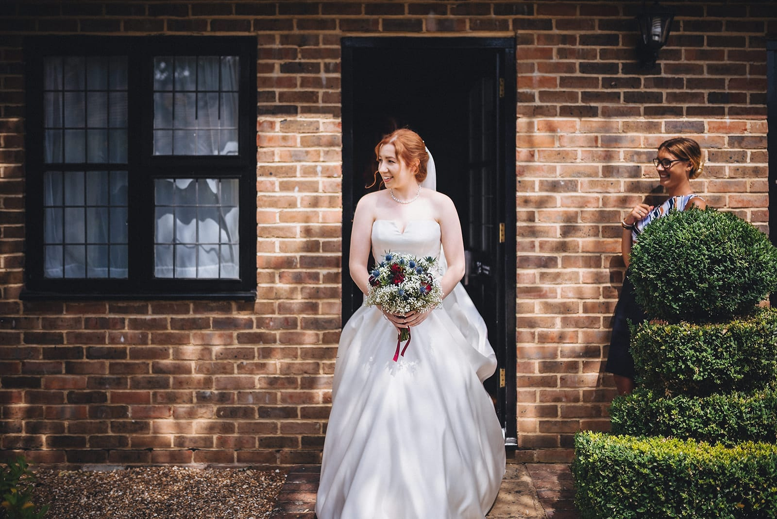 Bride walks out of her room towards her wedding ceremony at the Hever Hotel