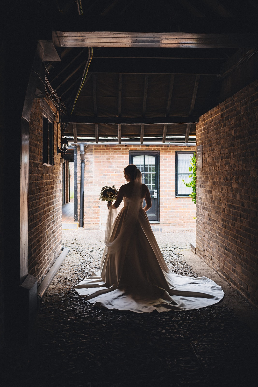 Bride walks down a dark covered pathway towards her microwedding at the Hever Hotel in Kent