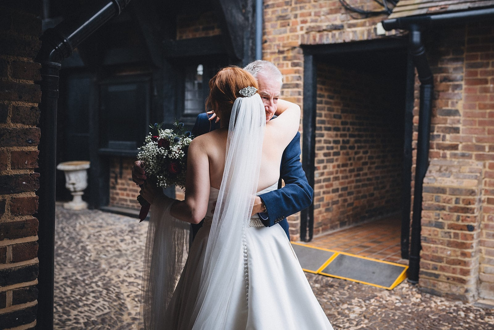 Bride and the father of the bride hug as he sees her for the first time
