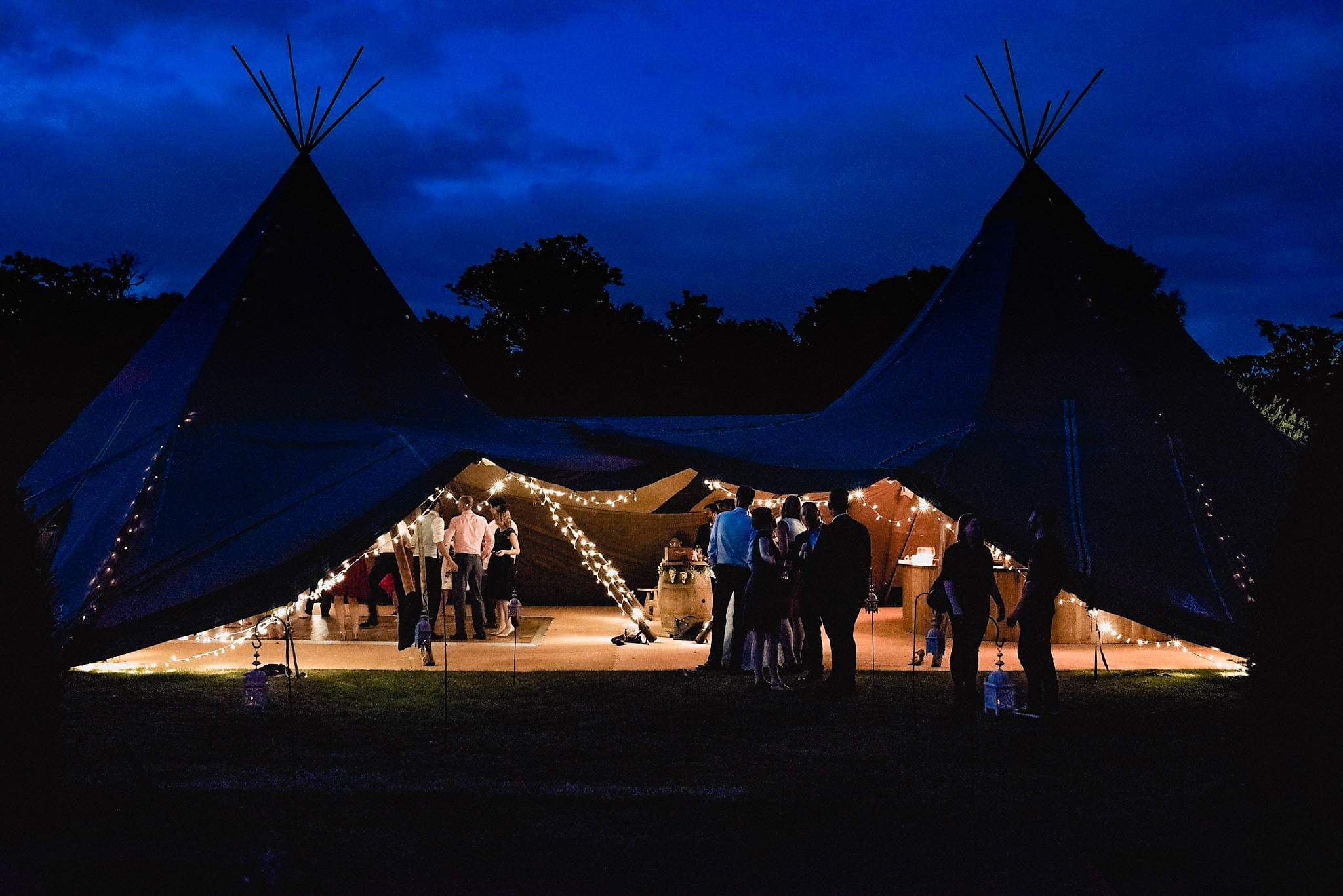 Tipi lit up at night and wedding guests stand in front and inside it