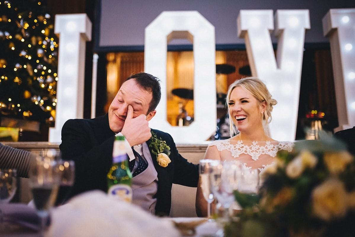 Bride and Groom laughing at speeches at their Salomons Estate Christmas Winter Wedding
