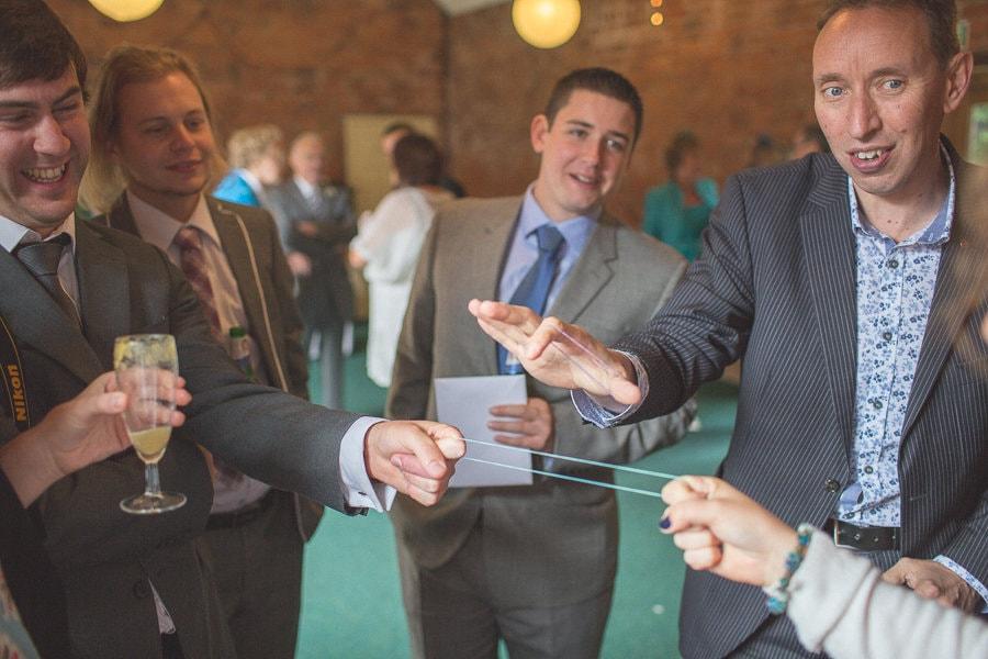 Magic tricks at a summer rustic Kent barn wedding