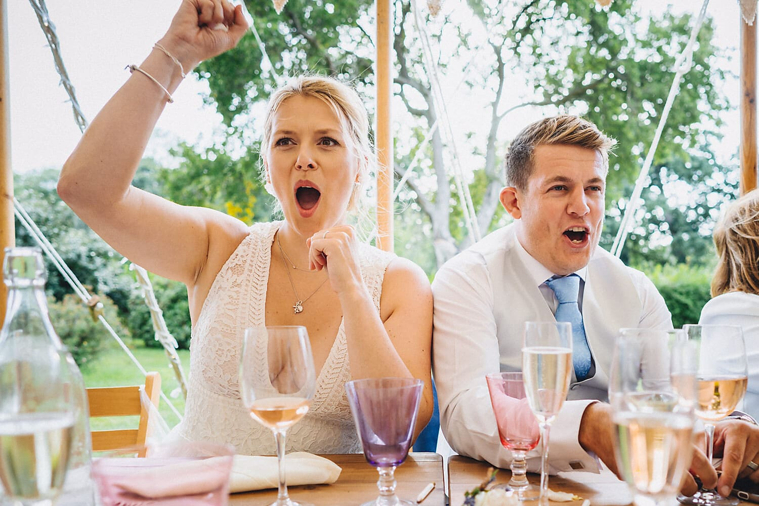 Bride and Groom cheering at the end of the speeches at their Littlefield Manor Summer Wedding