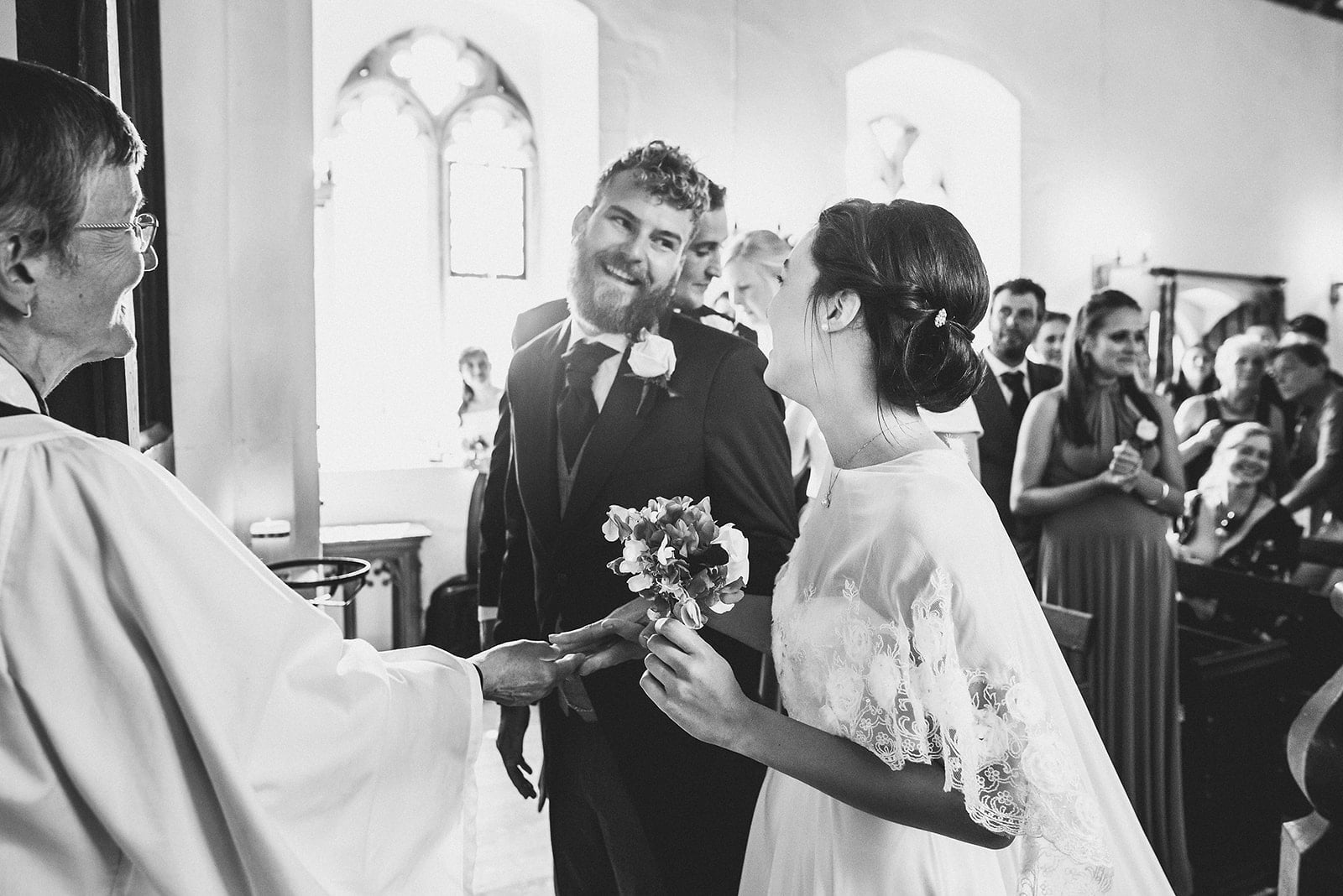 Bride and groom smile at each other at the top of the Church aisle
