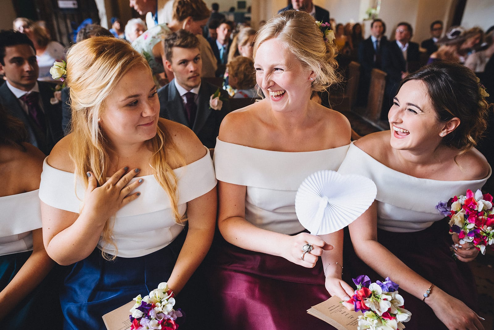 Bridesmaids smile emotionally at the end of the wedding ceremony