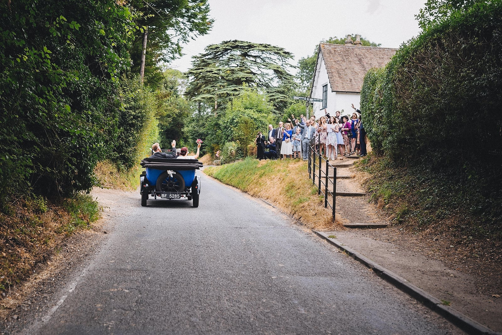 Bride and Groom wave at their guests as they drive away from their ceremony in their wedding car