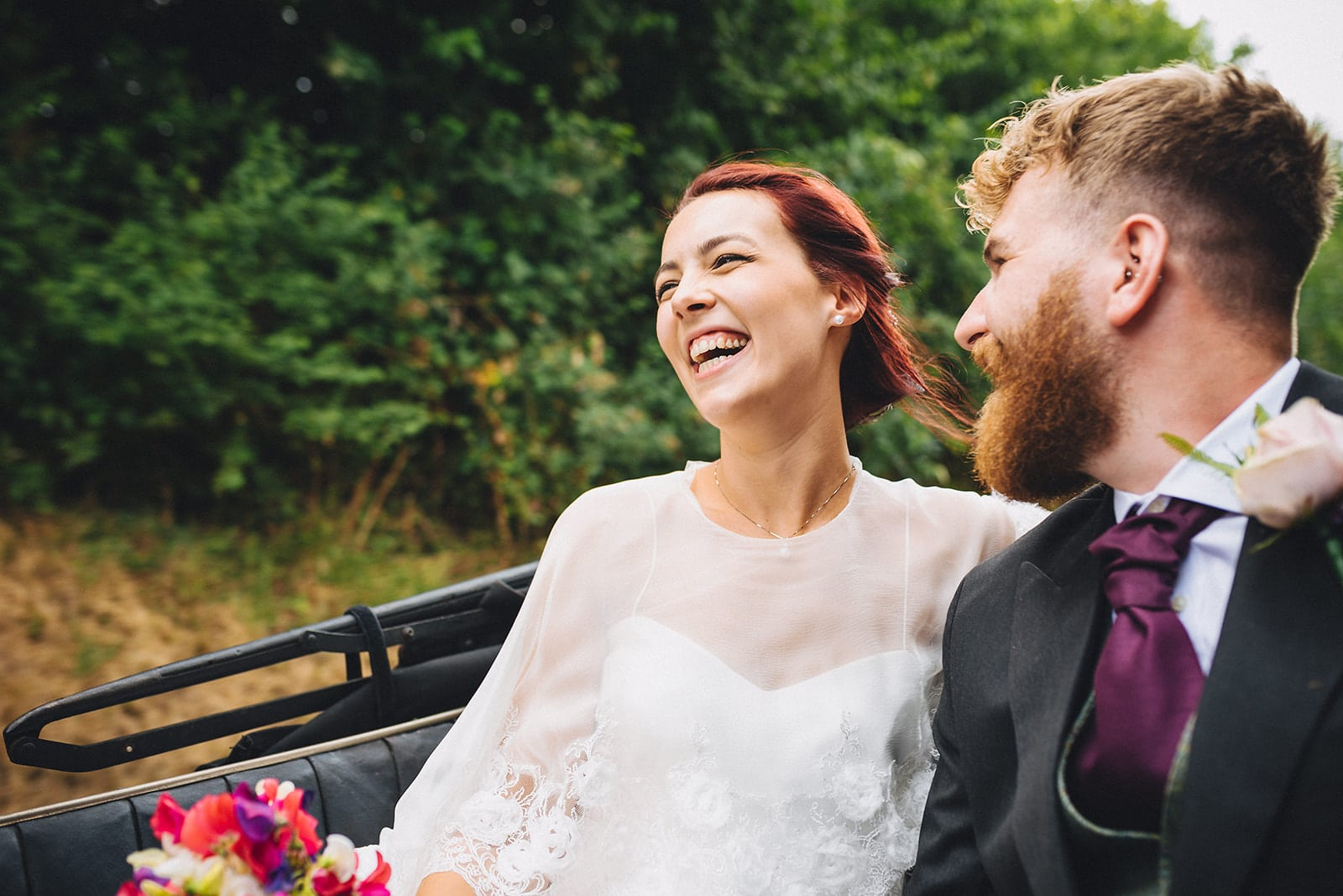 Bride and Groom laughing as they drive away from their Cambridge wedding ceremony
