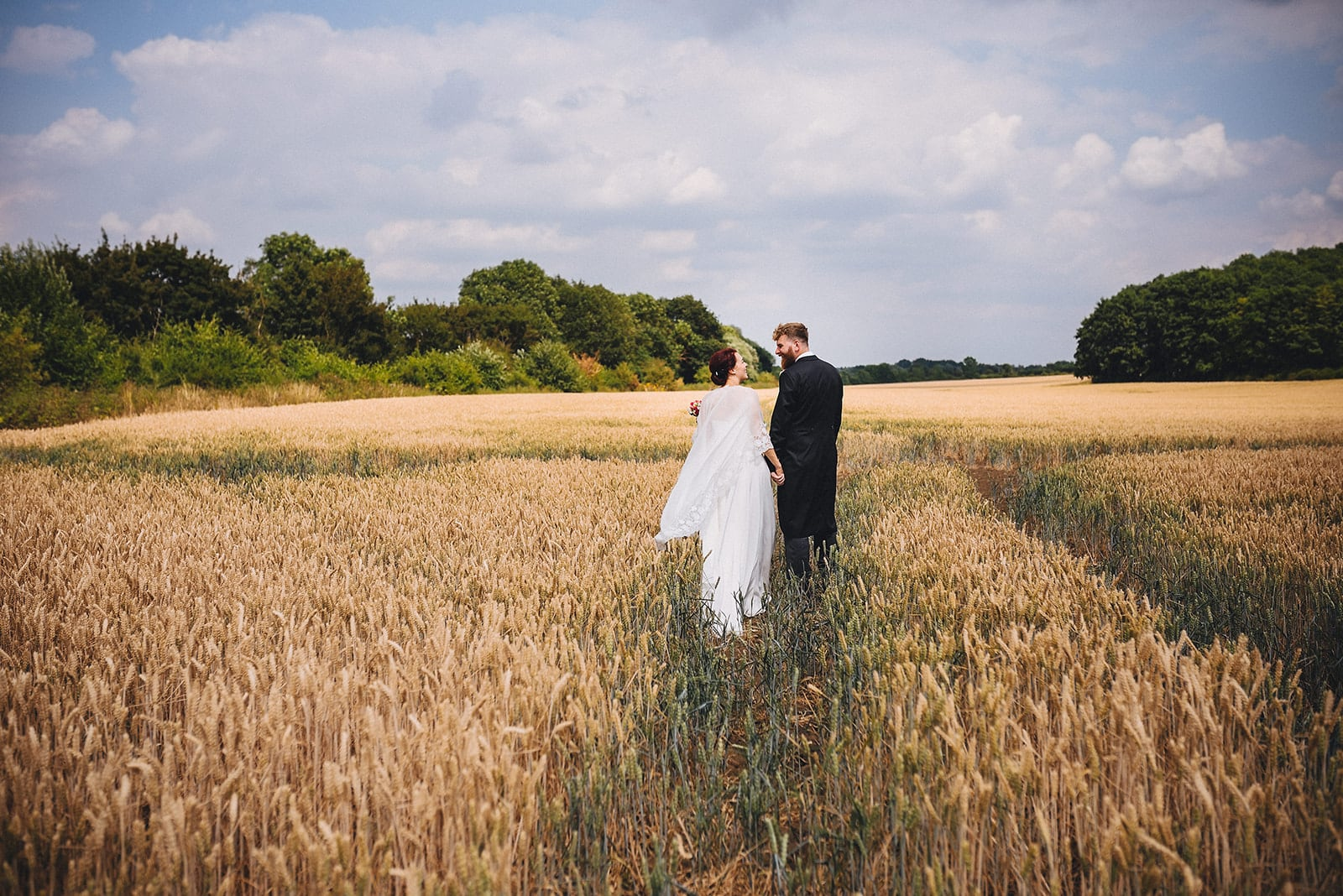 Bride and Groom walking into a corn field at their Joyful Cambridge Farm Wedding