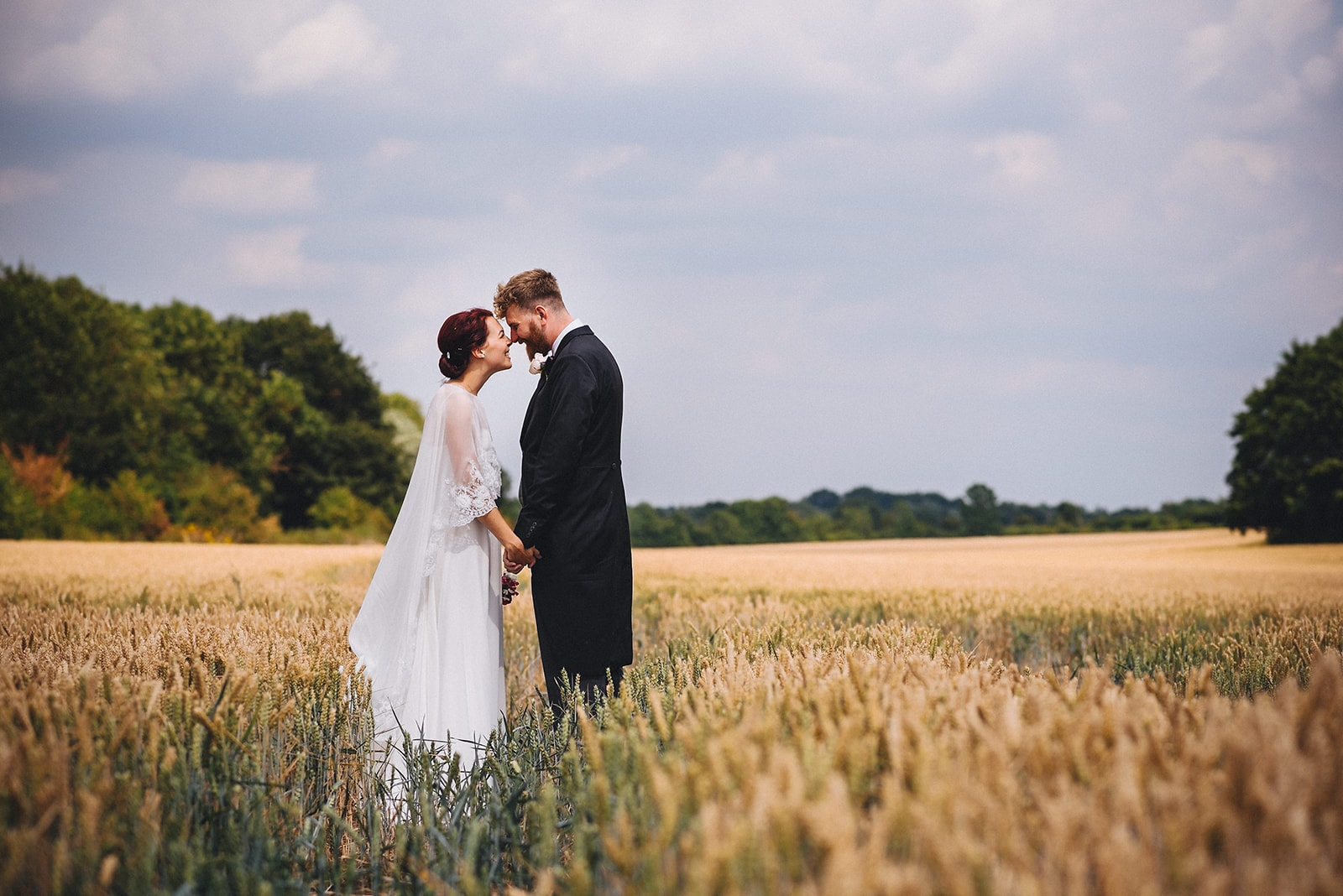 Bride and groom holding hands in a corn field at their joyful Cambridge Wedding