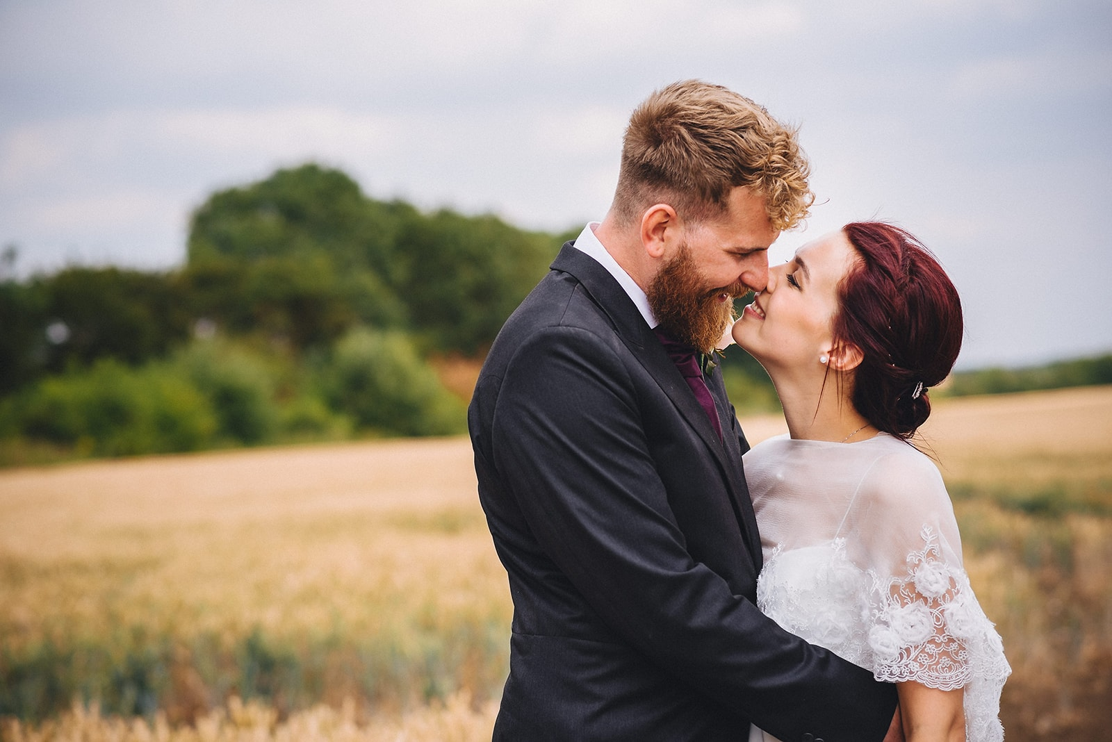 Bride and Groom rub noses in a field at their Cambridge Farm Wedding