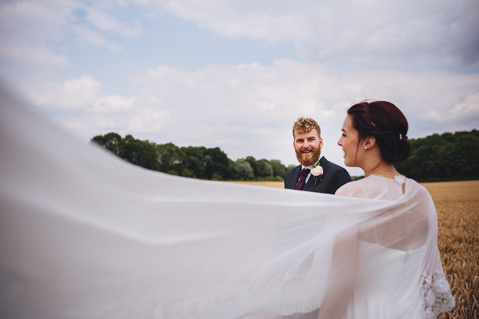 Groom lovingly looking at the bride as her veil blows across the field