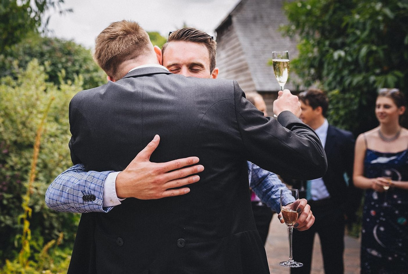Wedding guest tightly hugging the groom