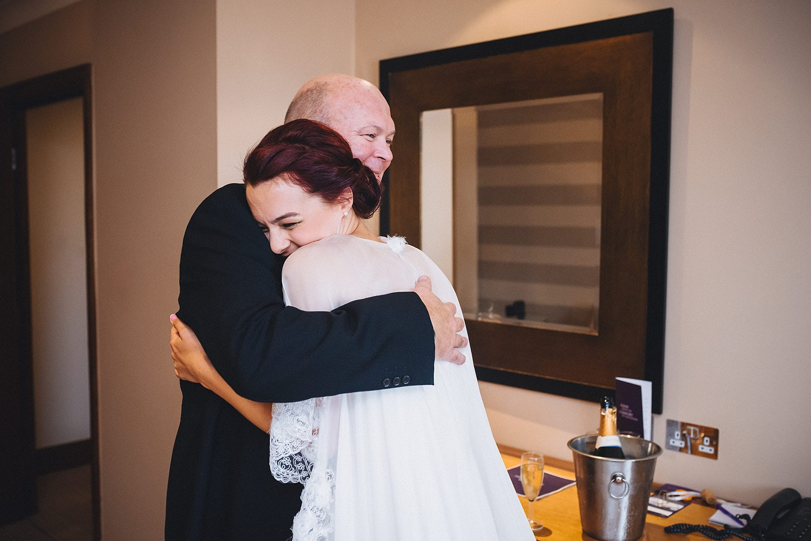 Bride and her dad hugging tightly