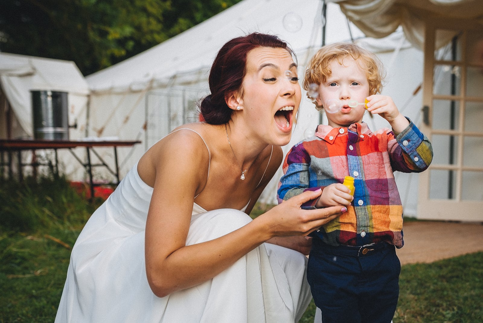 Bride blowing bubbles with a tiny wedding guest