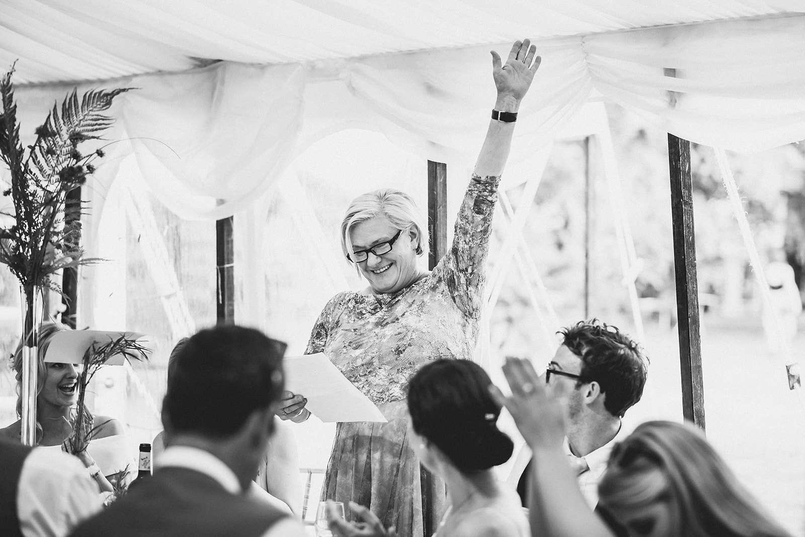 Mother of the groom cheering with her hand up during her wedding speech