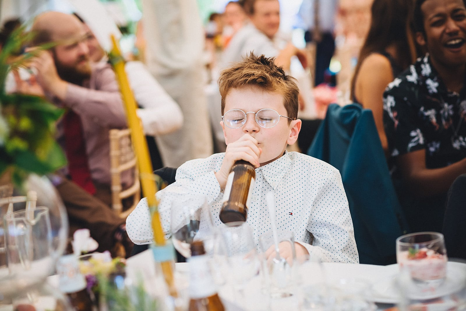 Little boy wedding guest drinking from a beer bottle during the wedding speeches