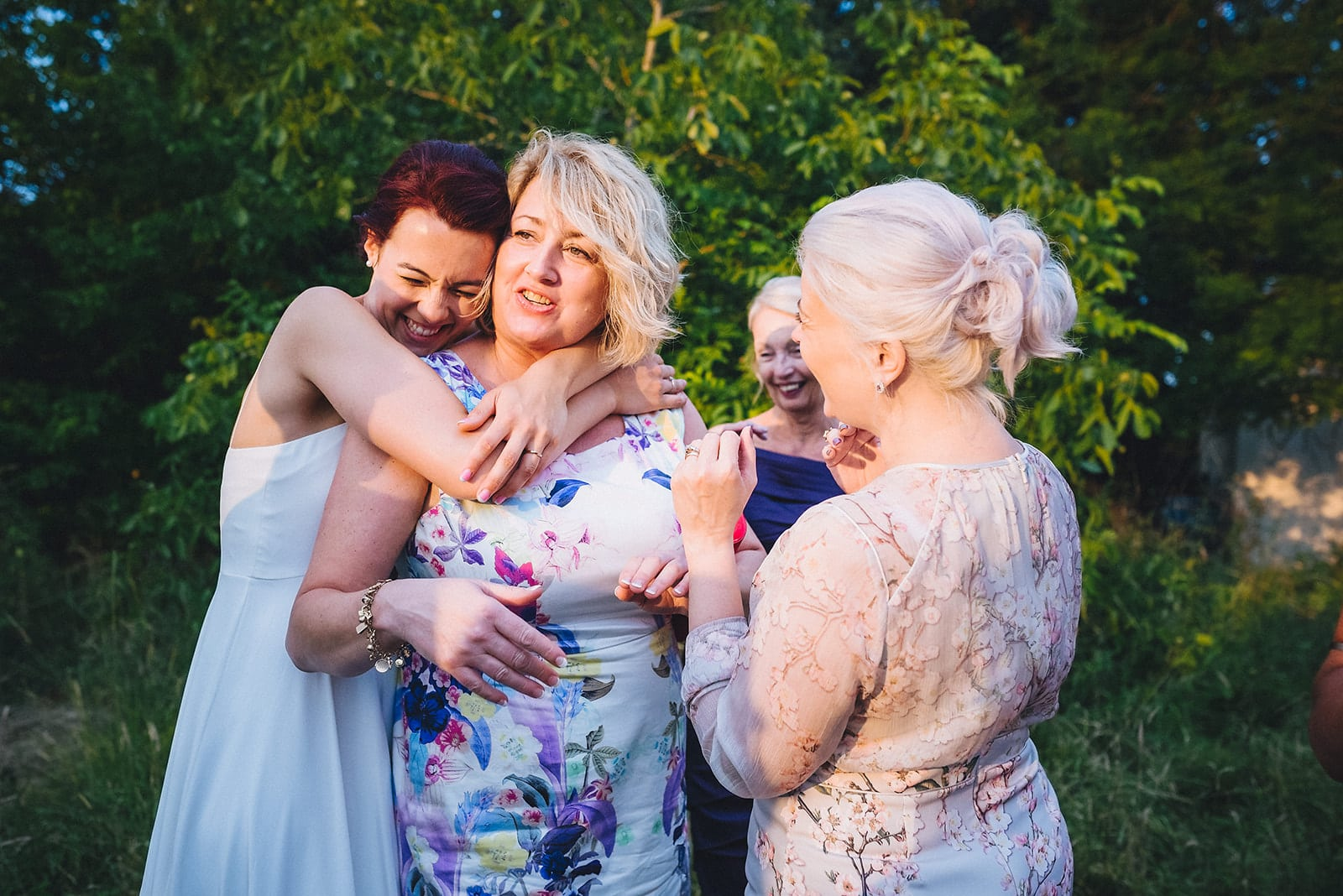 Bride hugs a wedding guest from behind with 2 other wedding guests smiling
