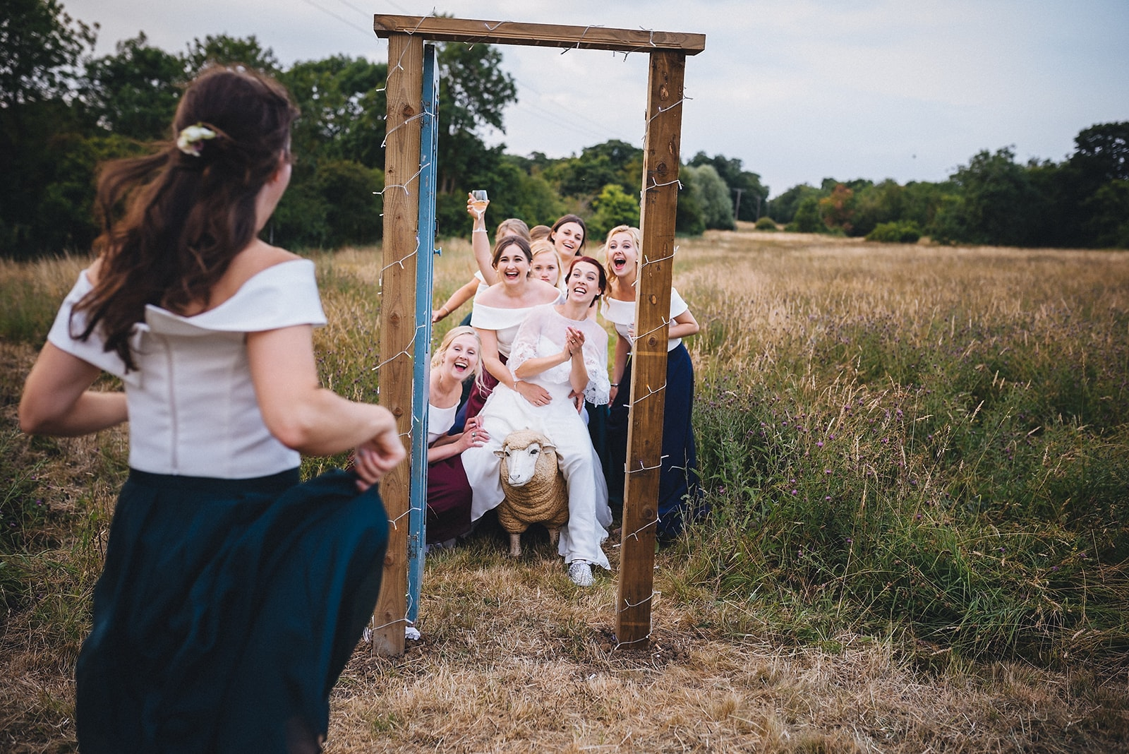 Bridesmaid runs to join the bride and bridesmaids in a field