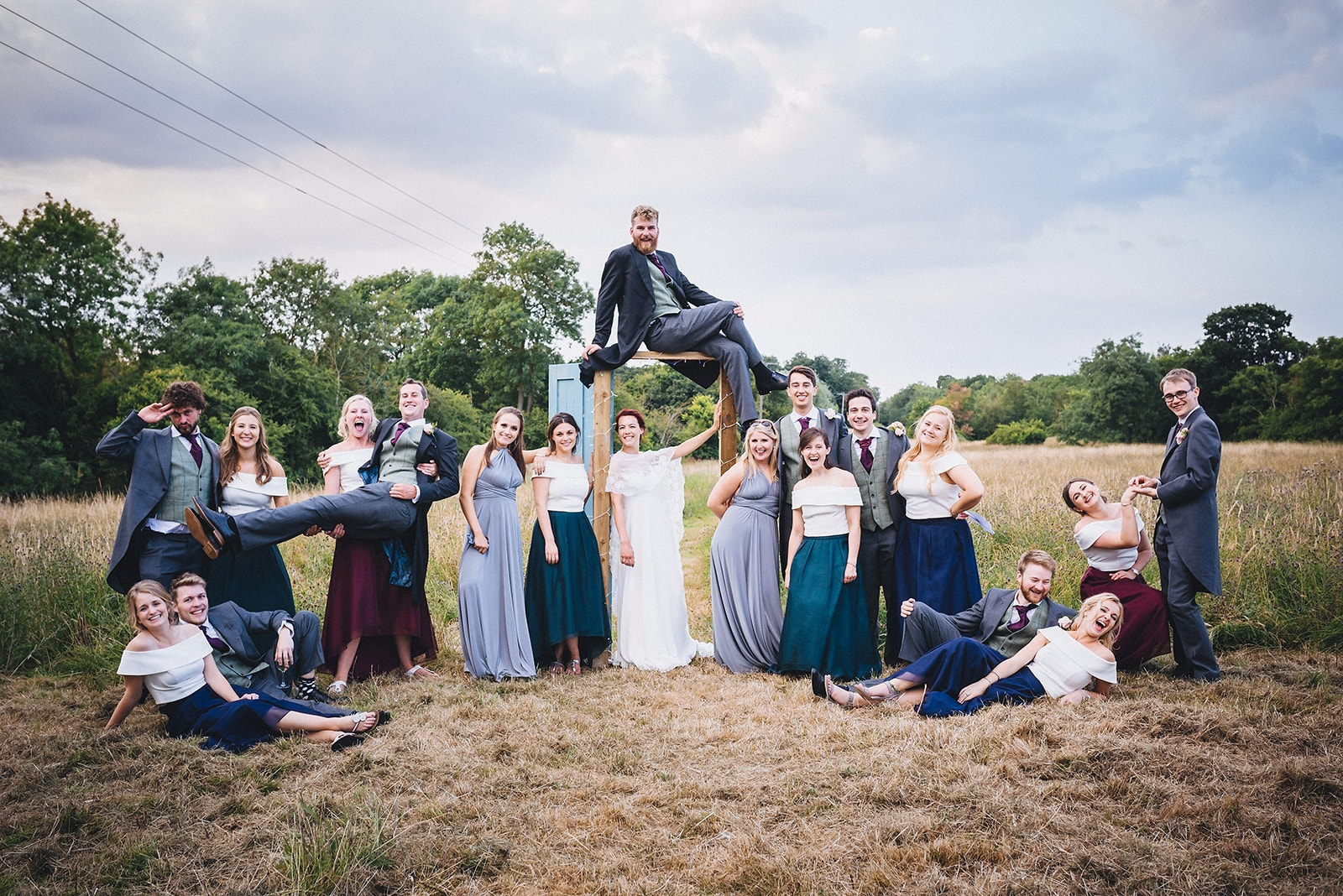 Bride, groom, bridesmaids and groomsmen pose in a fun group shot
