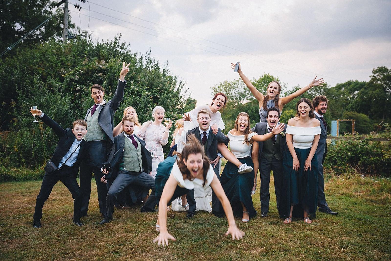 unposed natural fun group shot at a joyful cambridge farm marquee wedding
