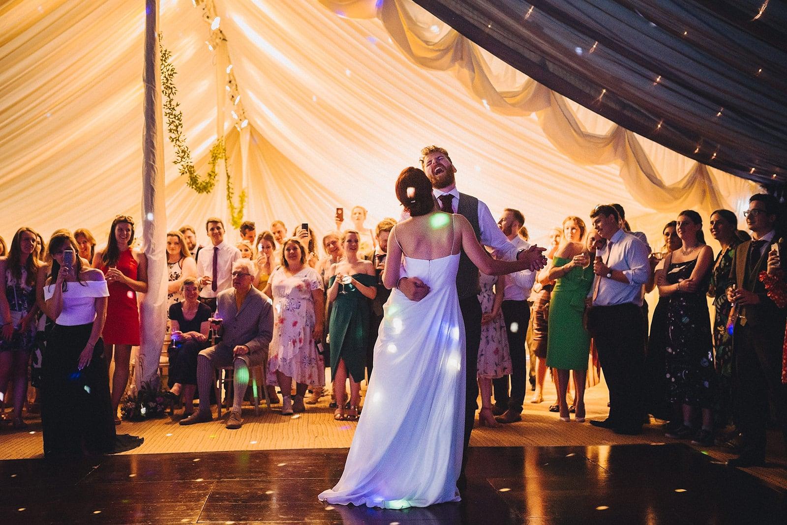 Bride and groom first dance at their joyful cambridge farm marquee wedding