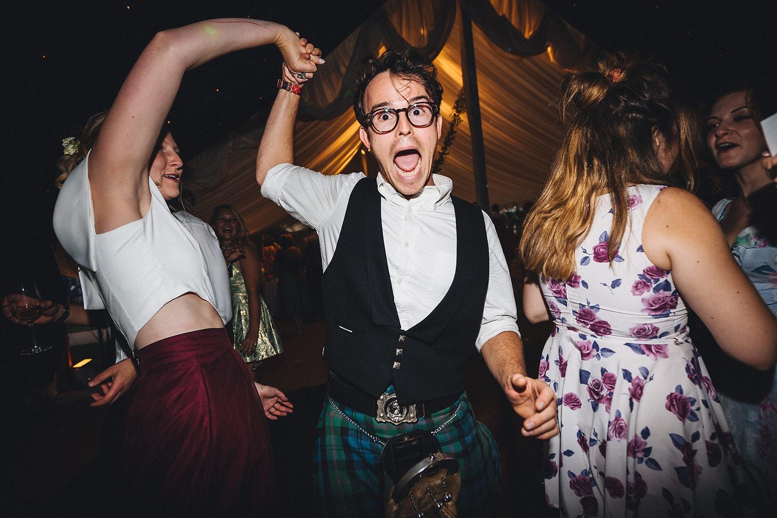 Wedding guests dancing singing loudly at a joyful Cambridge wedding