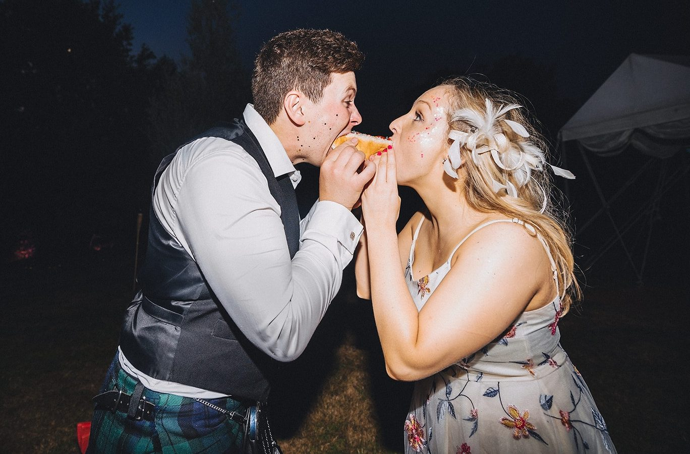 A man and woman share a hotdog at a wedding