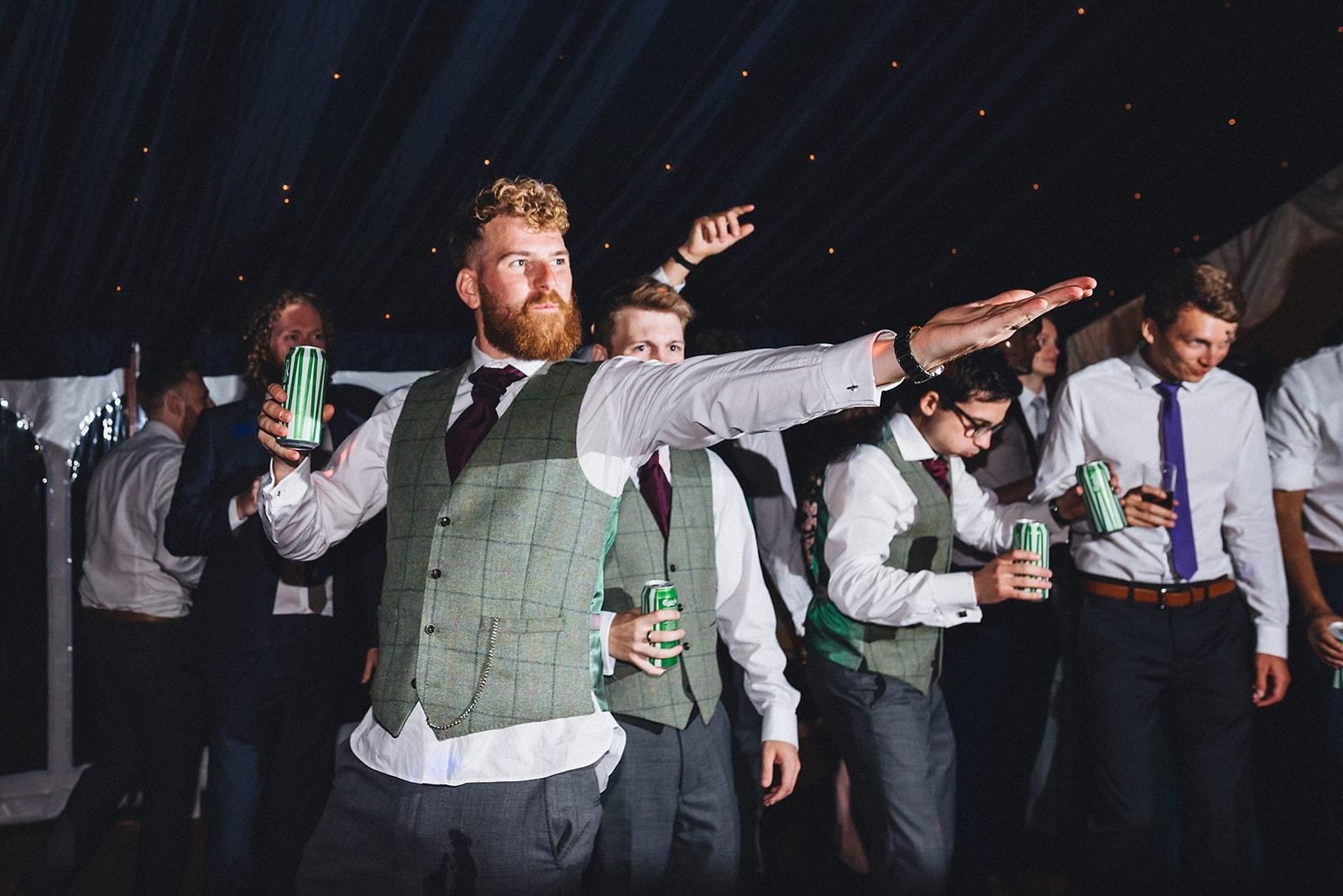 Groom and groomsmen drinking beer on the dance floor