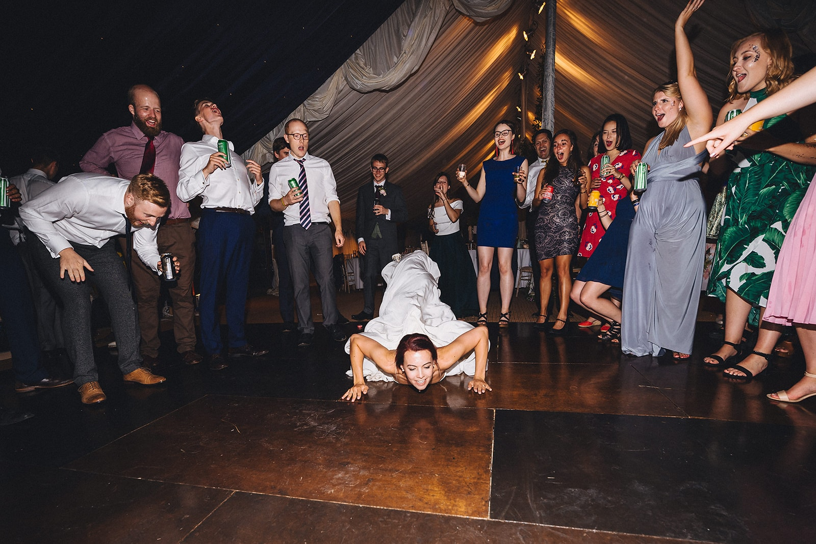 Bride doing the worm on the dance floor at her joyful cambridge farm marquee wedding