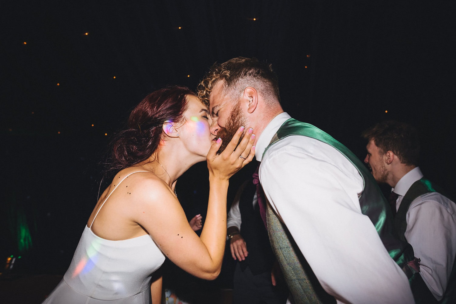 Bride and groom kiss intensely during their first dance