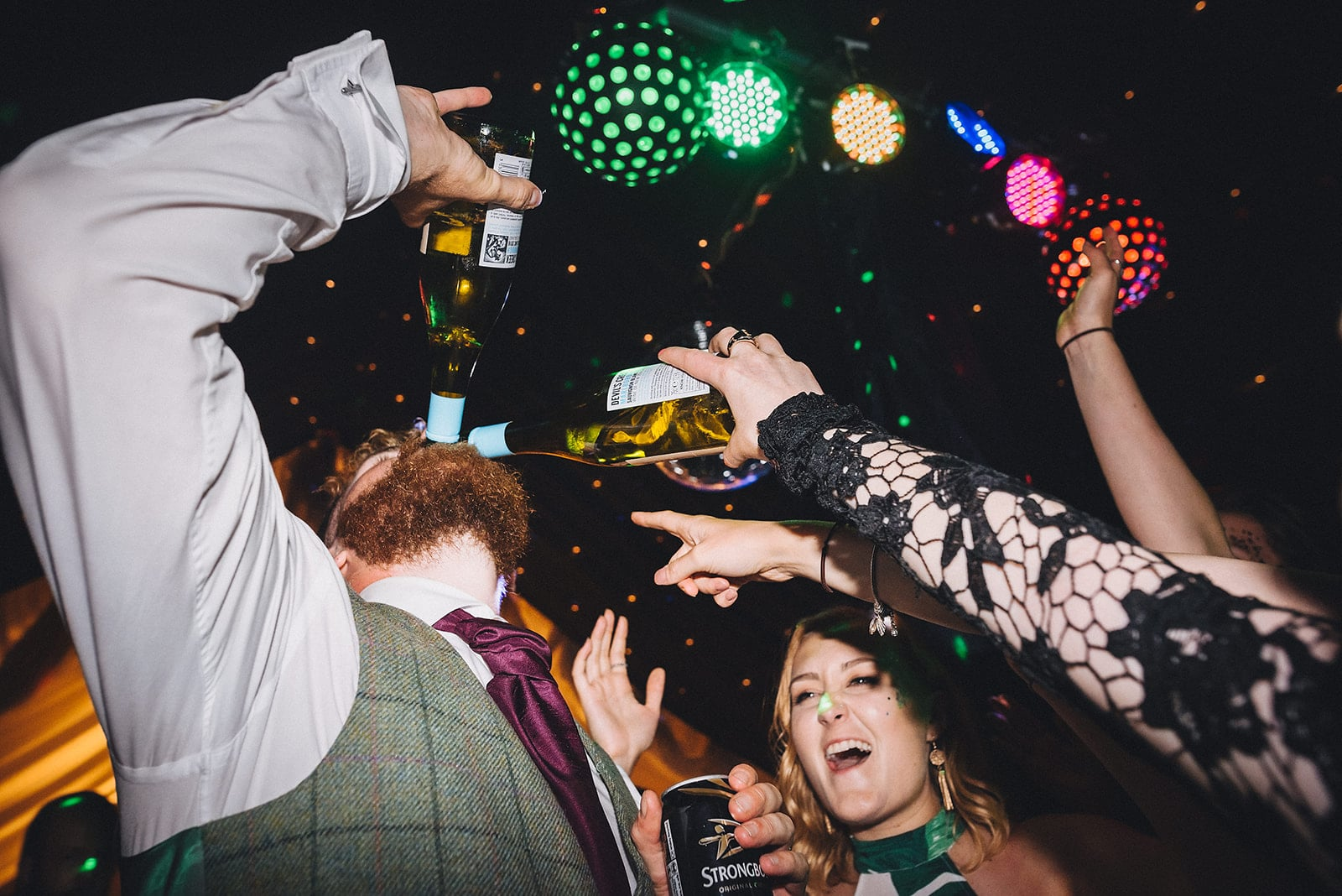 Groom drinking from 2 wine bottles with guests cheering on at his Cambridge Farm Marquee Wedding
