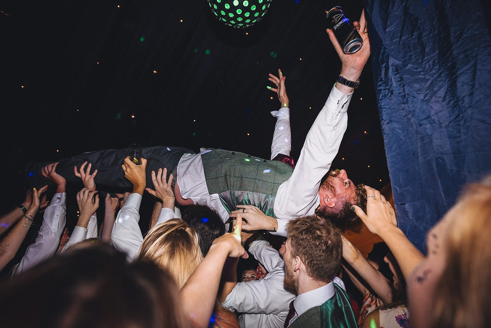Groom crowdsurfing held up by lots of hands
