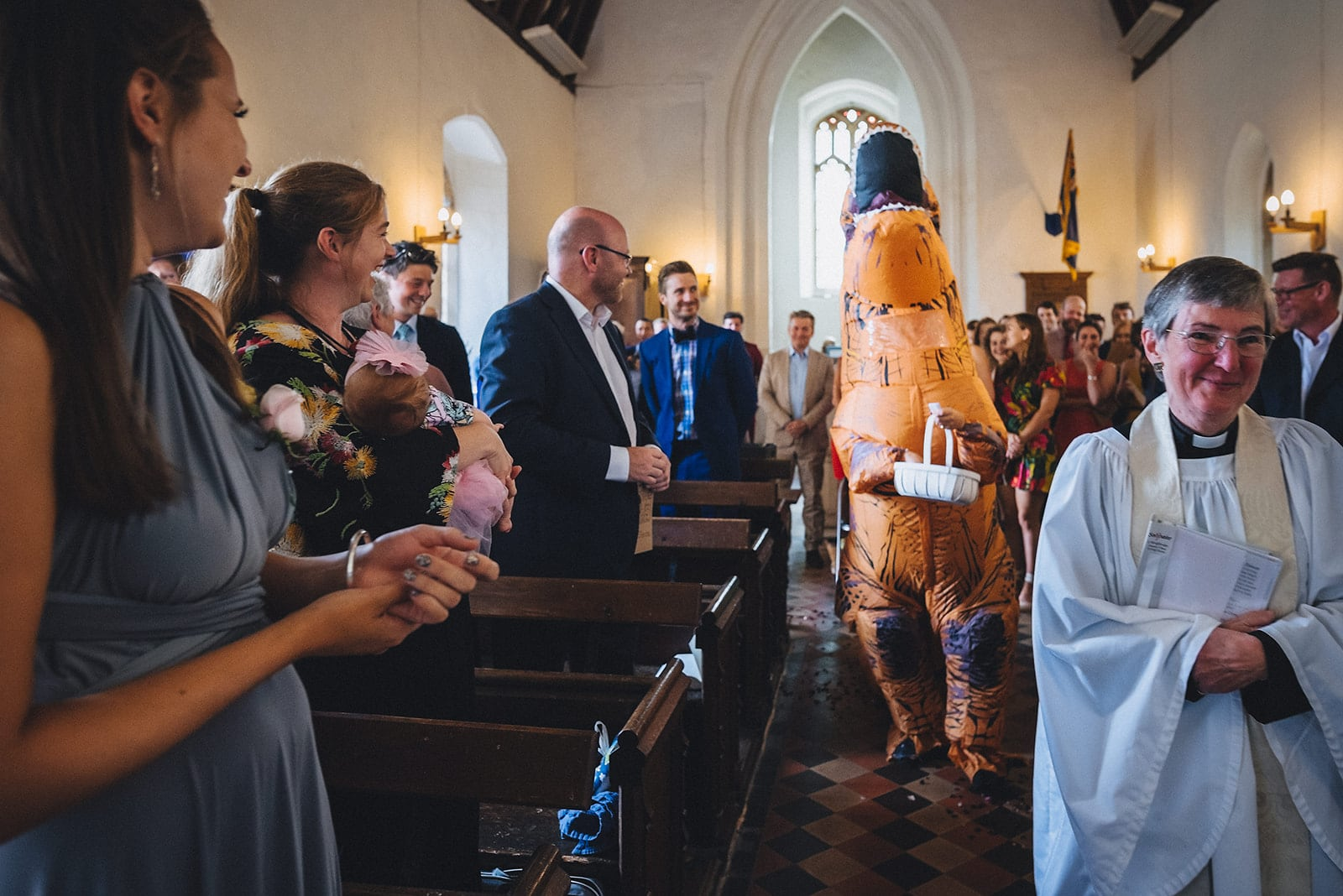 Dinosaur flower girl walking down the aisle after the vicar