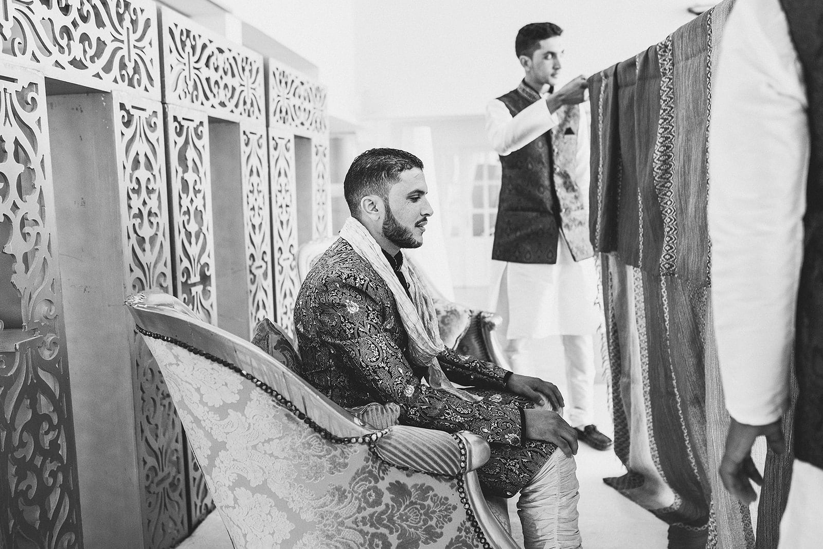 Moroccan Berber Groom sitting behind a traditional curtain while his bride walks into the Nikkah