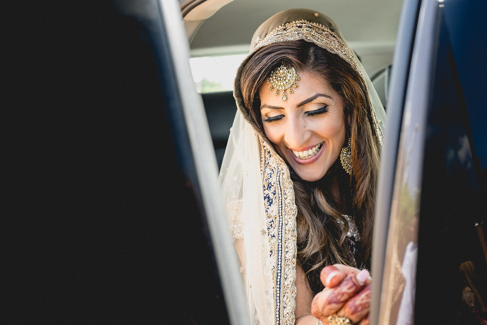 Asian bride smiles as she gets into her car at her Marrakech Destination wedding