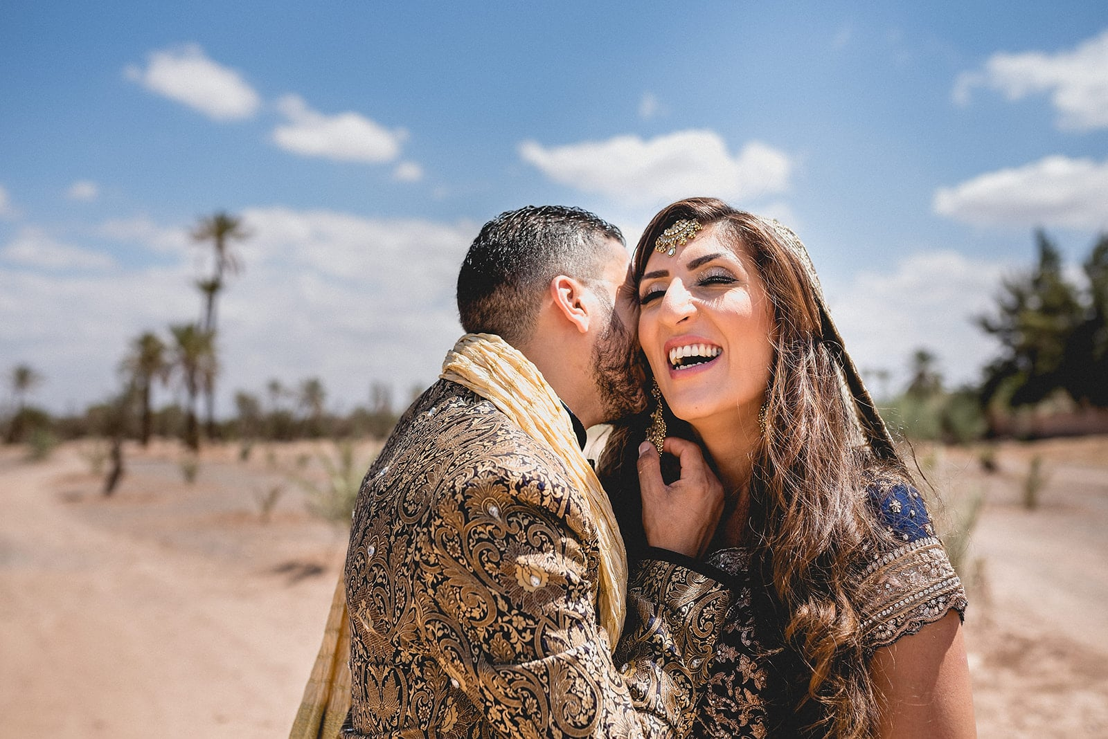 Moroccan Groom whispers into his bride's ear and pulls on her earring while she laughs in the Sahara desert