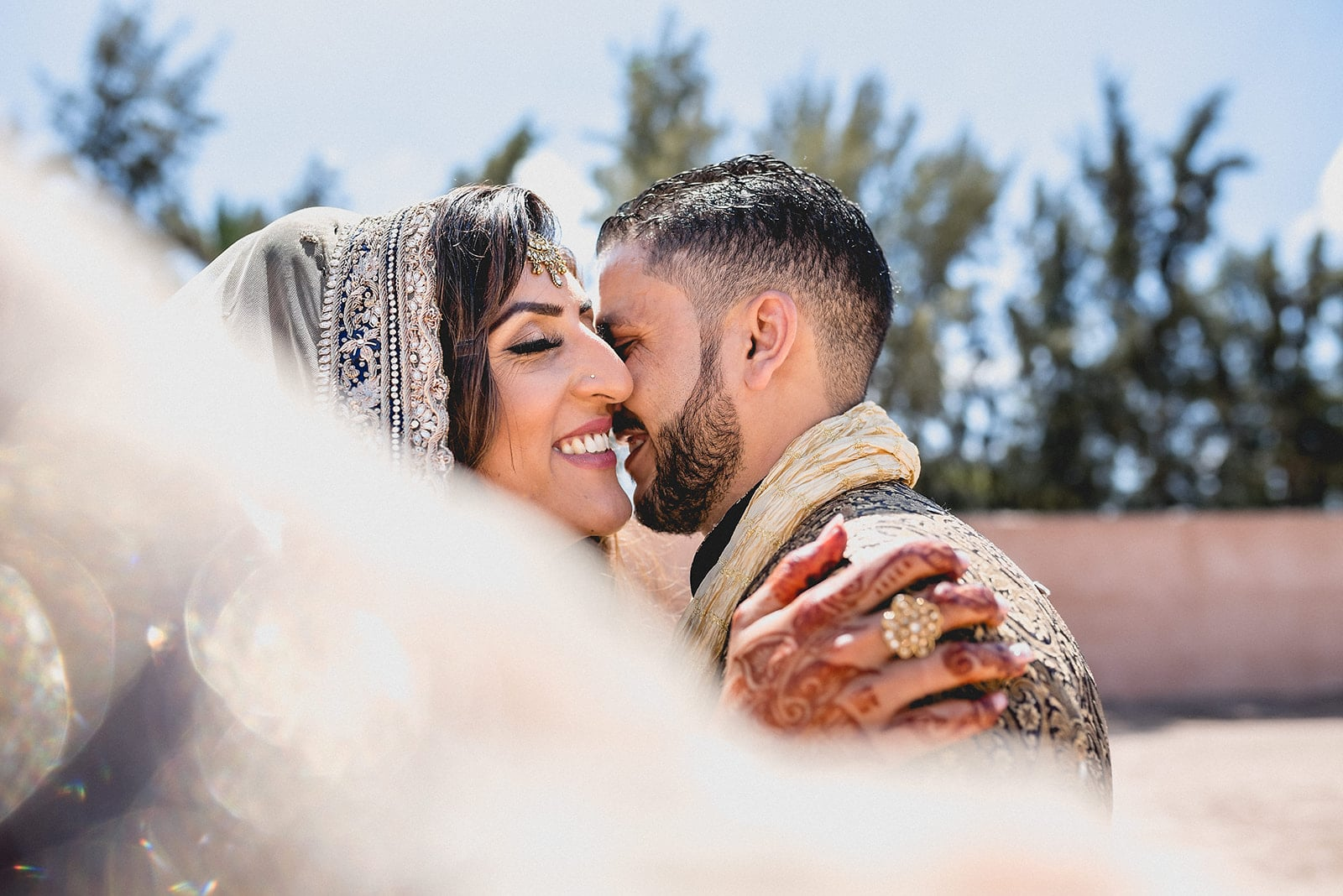 Moroccan Bride and groom laugh with each other while the wind blows through her wedding head scarf in Morocco