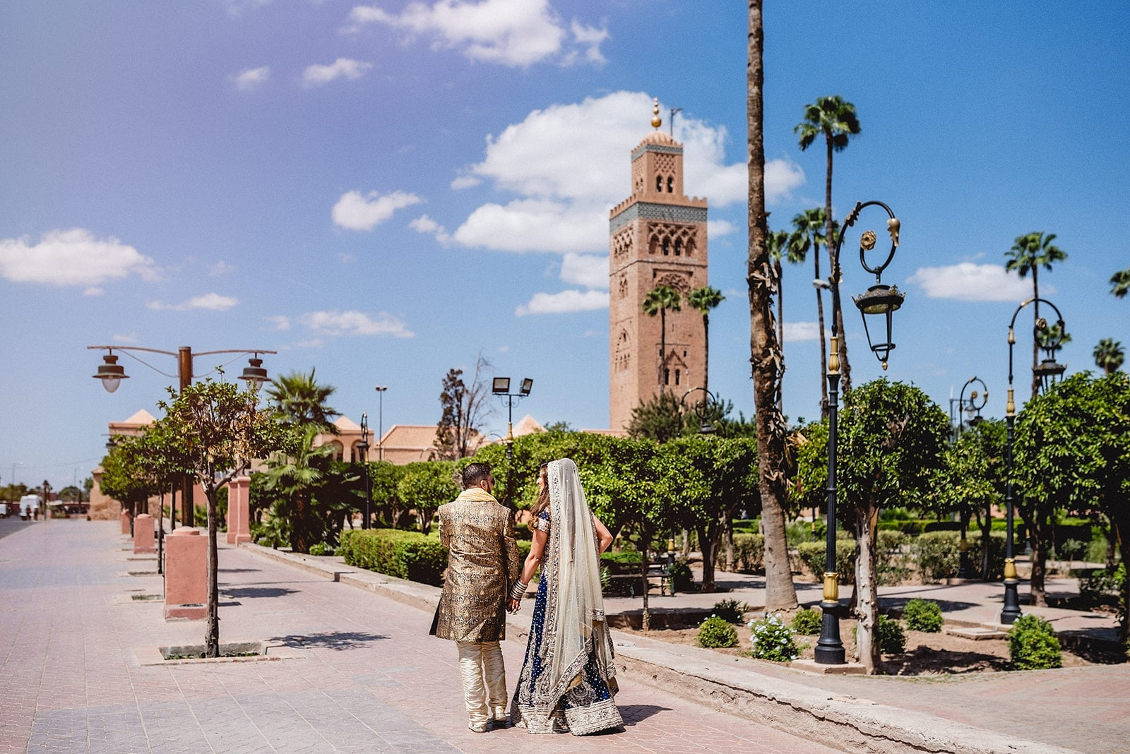 Moroccan couple walking towards the Koutoubia Mosque in Marrakech