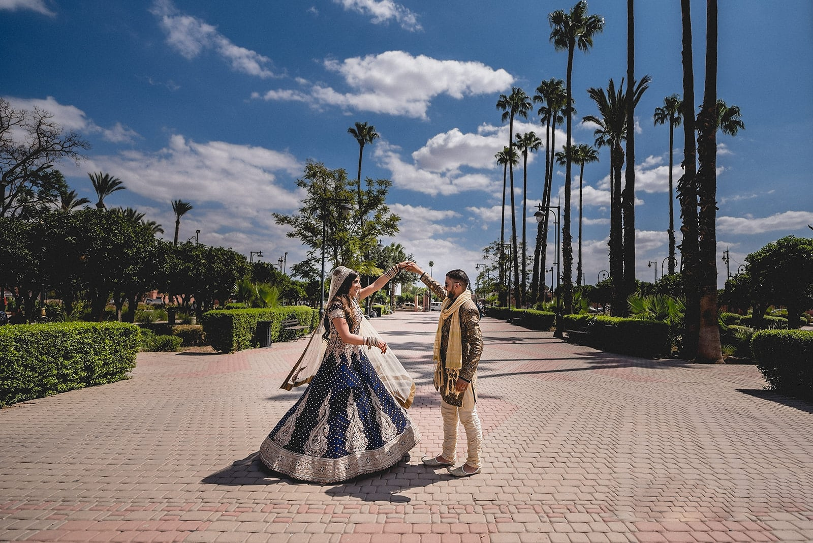 Berber Moroccan Groom twirling his Asian Bride to see the beauty of her deep blue wedding dress in the gardens of Koutoubia Mosque