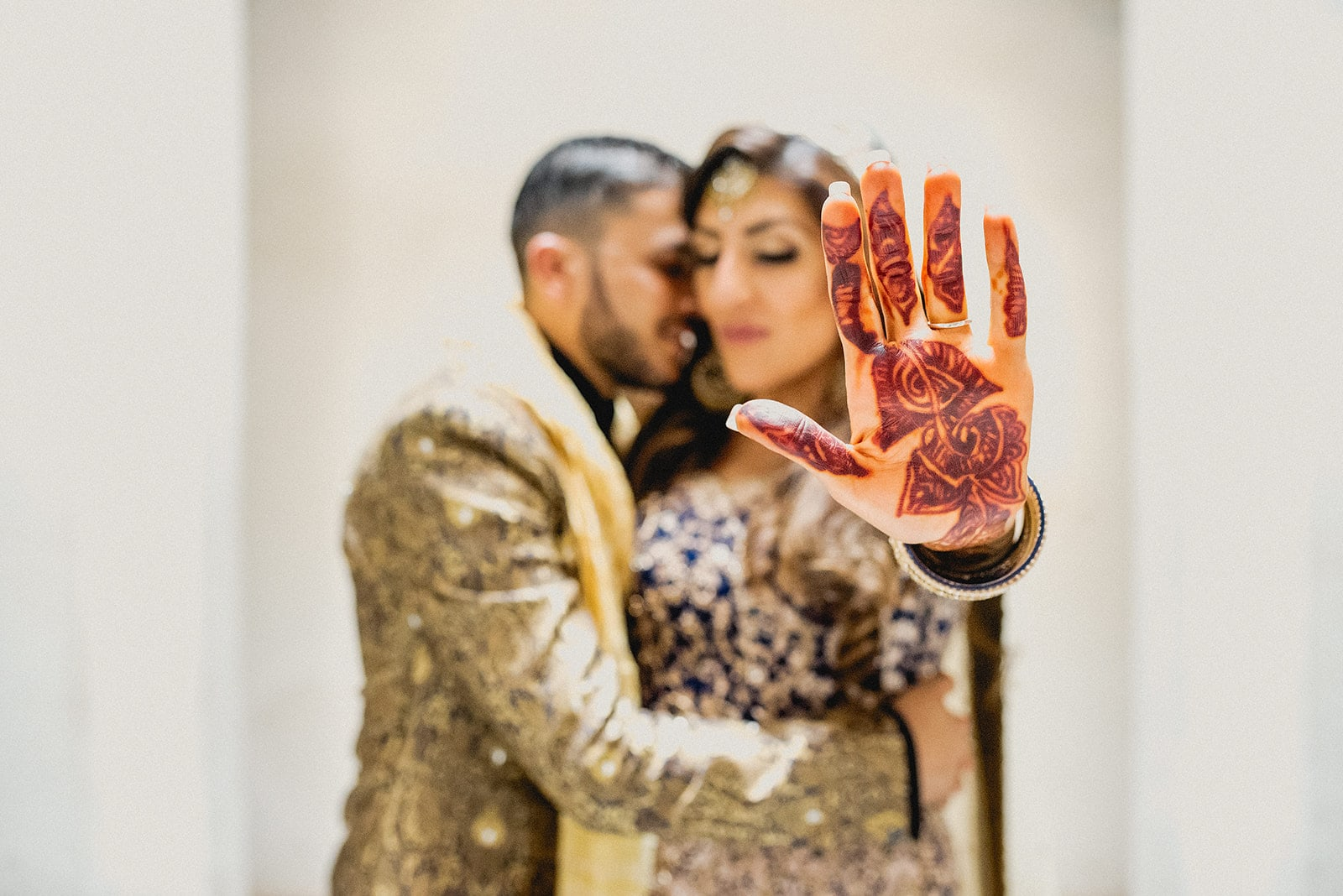 Asian Bride hold up her henna painted hand while she and her moroccan groom hug in the background