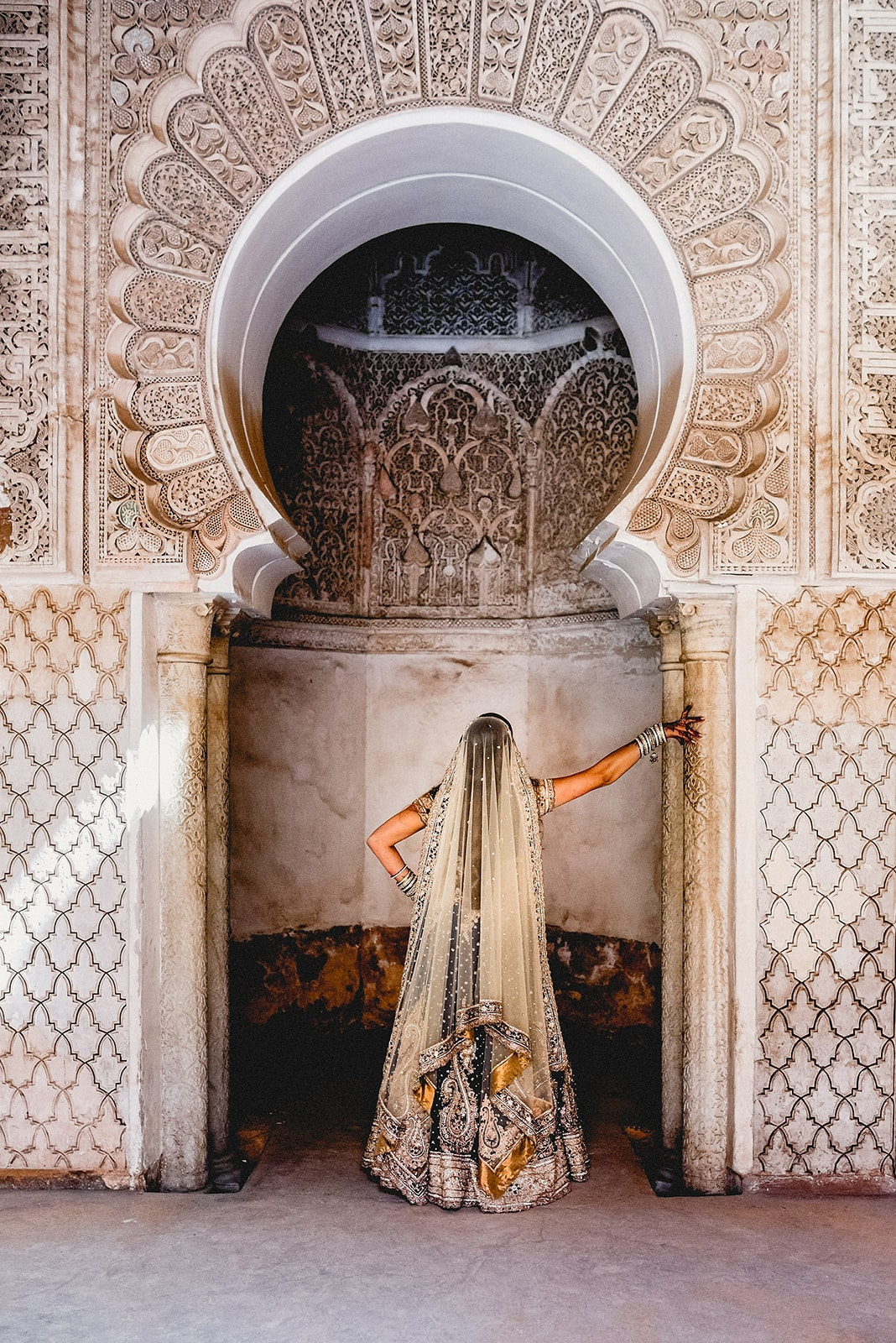 Bride admires the carvings in an archway at Ben Youssef Madrassa