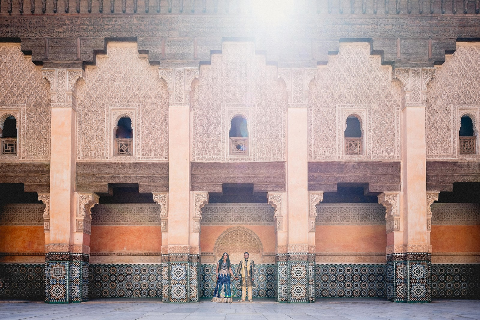 Bride and Groom holding hands in the central arch at the Ben Youssef Madrassa at their Moroccan Destination Wedding in Marrakech