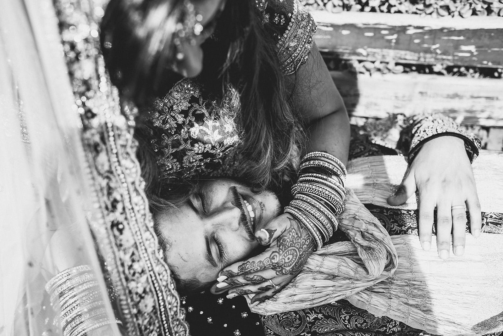 Bride lovingly strokes her Moroccan Groom's face with her henna covered hands while he smiles at their Traditional Moroccan Destination Wedding
