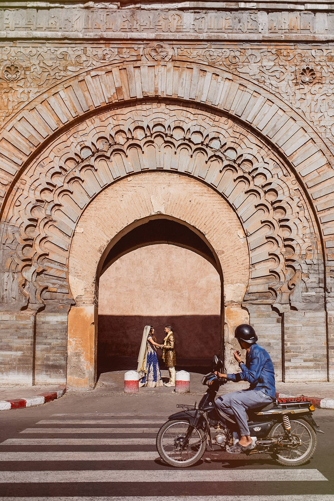A Motorcyclist looks at the wedding couple standing in the centre of the Bab Agnaou city gate in Marrakech