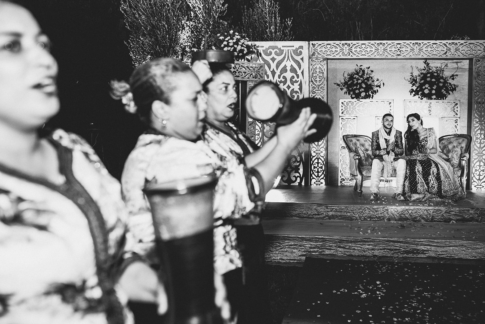 Asian bride and groom sit on the stage while the Moroccan band drums and sings in front of them at their Traditional Moroccan Destination Wedding
