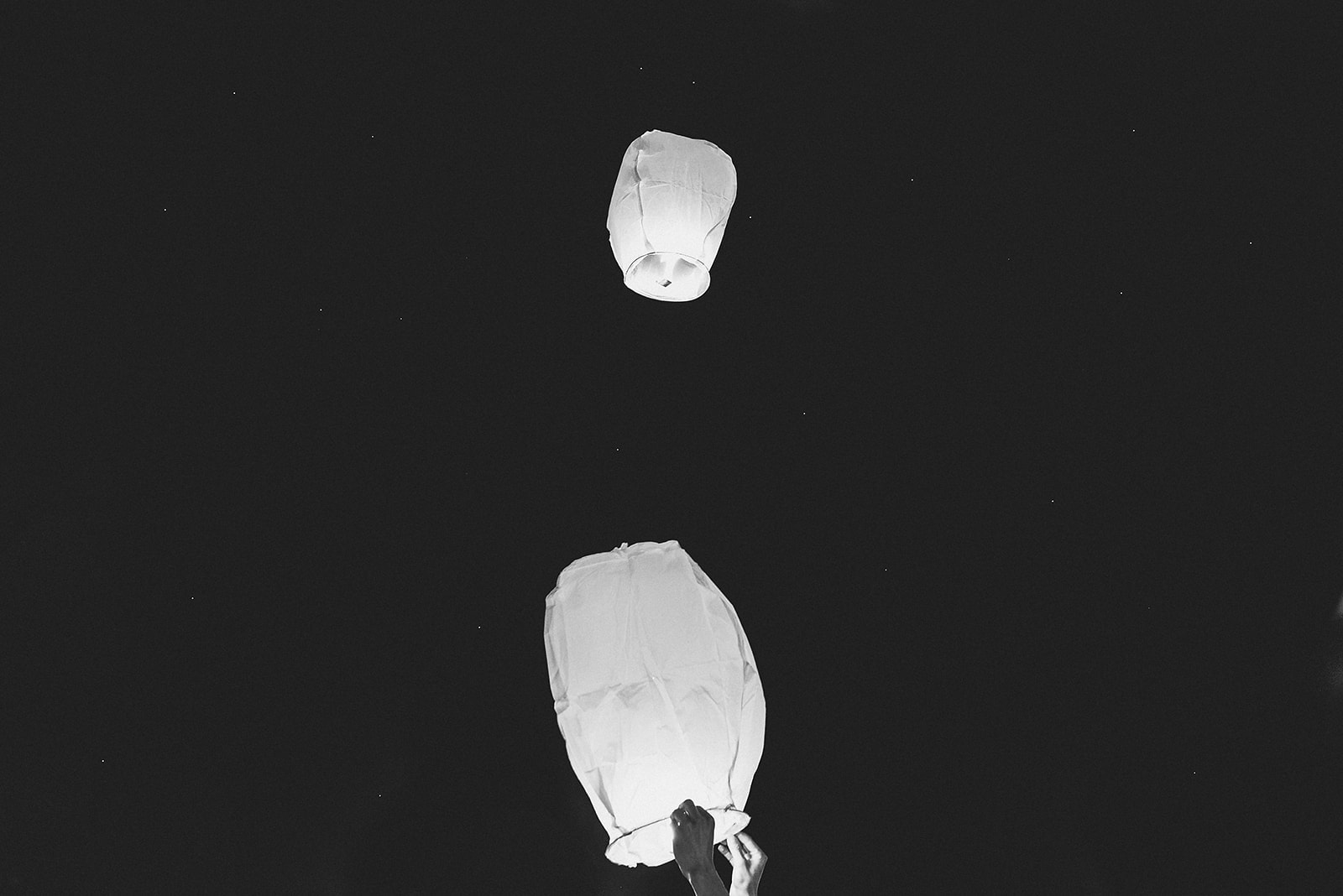 Bride's hands as she releases Chinese paper lanterns and they float across the Sahara Desert in Morocco