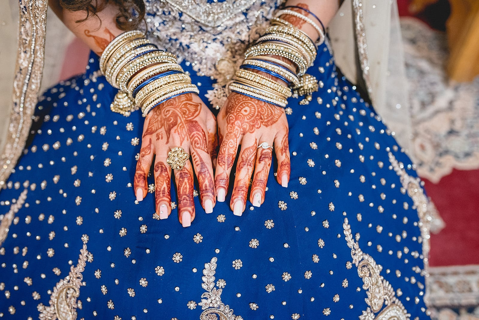 Bride's henna painted hands lying in her lap with traditional wedding bands