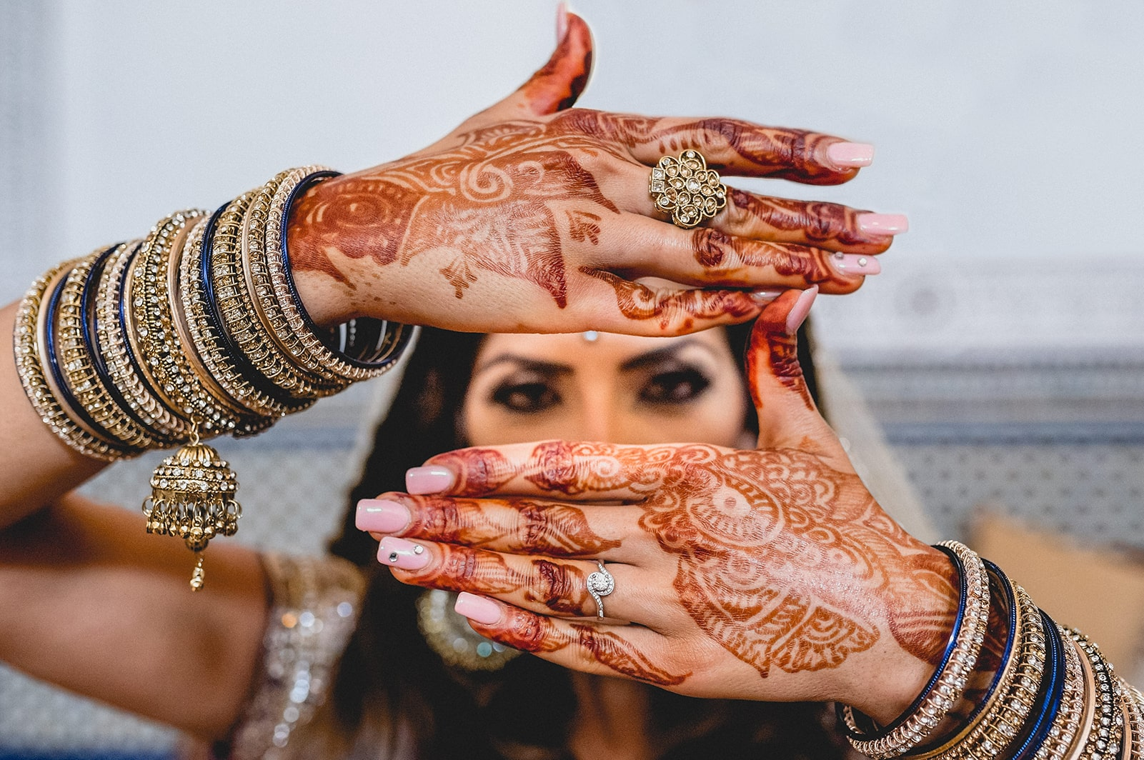 Moroccan Bride holding her henna painted hands in front of her face so only her eyes show
