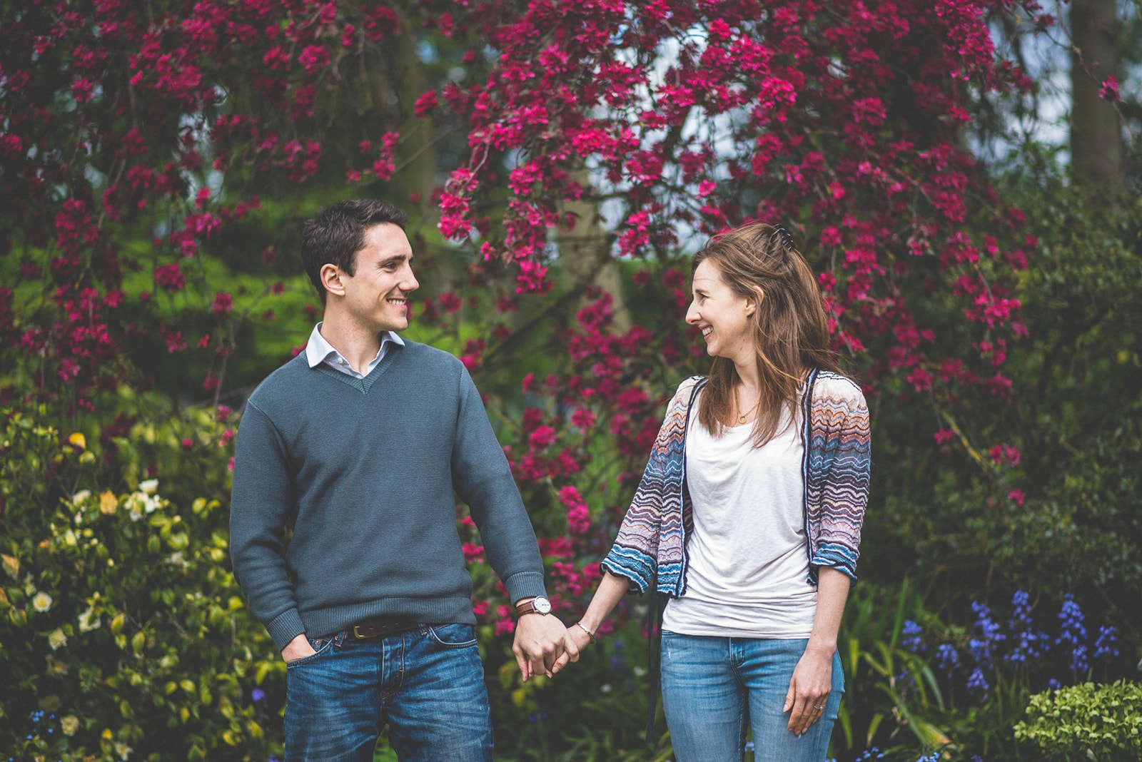 Young couple hold hands on their Colourful Spring Engagement Shoot at The Hurlingham Club