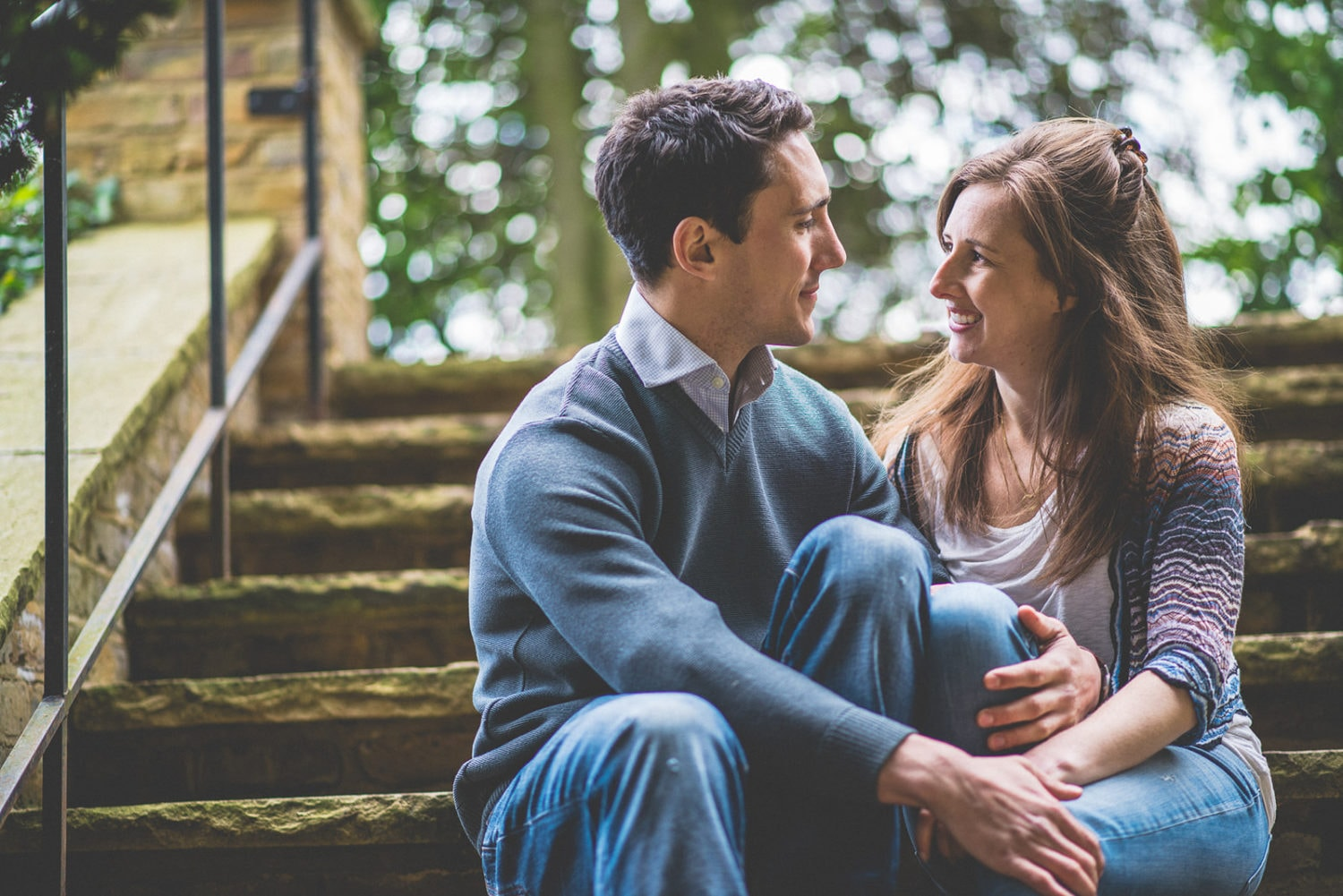 young engaged couple sit on steps and look at each other